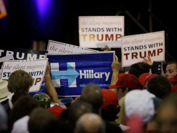 A woman holds up a sign for Democratic presidential candidate Hillary Clinton during a rally for Republican presidential candidate Donald Trump. AP Photo/Jae C. Hong.